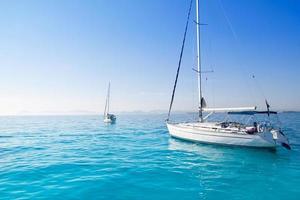 barche a vela ancorate nella spiaggia turchese di Formentera foto