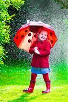 bambina carina con l'ombrello che gioca sotto la pioggia
