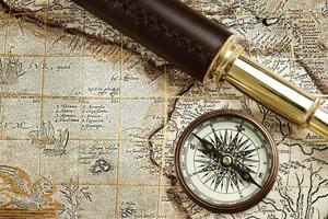 antico equipaggiamento da viaggio: cannocchiale in ottone e bussola sulla vecchia mappa