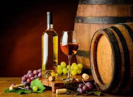 vino bianco e uva con botte foto