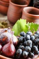 fichi maturi e uva su un piatto di argilla foto