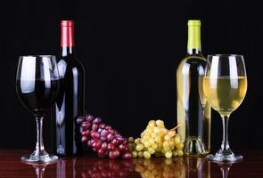 bottiglie di vino e bicchieri di vino sul nero foto