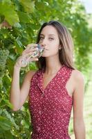 felice giovane donna con in mano un bicchiere di vino bianco foto
