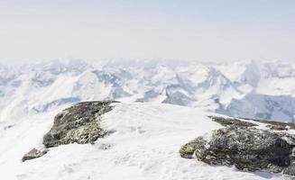 roccia innevata con vista sulle montagne nella parte posteriore foto