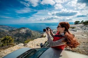 fotografo donna con auto sulla cima della montagna