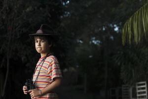 ragazzo con cappello da avventuriero a guardare con il binocolo.
