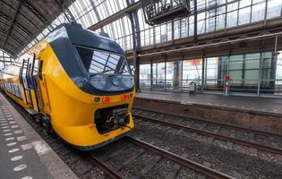 Il treno giallo si trova sulla stazione ferroviaria centrale di Amsterdam