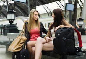 ragazze sedute alla stazione ferroviaria foto