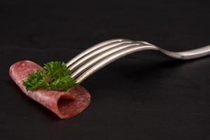 salame scheiben auf einer schwarzen platte