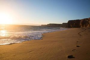 passi lungo la spiaggia al tramonto