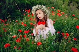 bella bambina in posa in una corona di gonna di papaveri