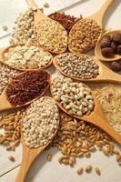 cereali, fagioli nei cucchiai sul tavolo di legno bianco