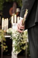 dolore - uomo con rose bianche al funerale dell'urna