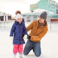 giovane padre e adorabile bambina sulla pista di pattinaggio