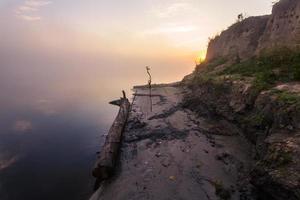 mattina nebbiosa sul fiume e nuvole riflesse nell'acqua