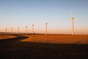 turbine che producono energia eolica in un bellissimo tramonto dorato foto