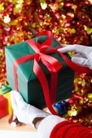 Babbo Natale che mostra una confezione regalo di Natale foto