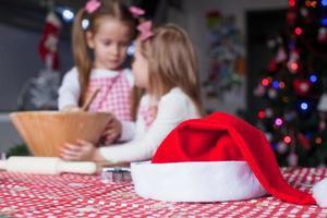 santa cappello sfondo di due bambina cottura biscotti di Natale