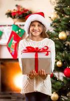 bambina felice che tiene grande confezione regalo di Natale
