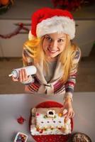 ragazza adolescente in santa hat decorare la casa dei biscotti di Natale foto