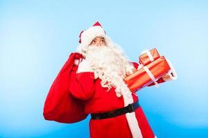 Babbo Natale con doni sulle mani su sfondo blu foto
