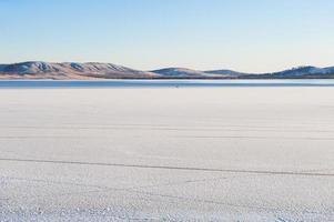 lago ghiacciato e montagne al tramonto. foto
