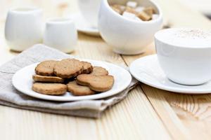 biscotti allo zenzero, cannella, una tazza di caffè caldo.