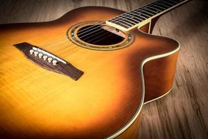 chitarra acustica in cima al tavolo di legno foto