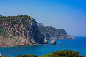 scogliera di montagna accanto al mare durante il giorno