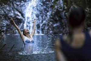attraente giovane donna fare il bagno vicino alla cascata.