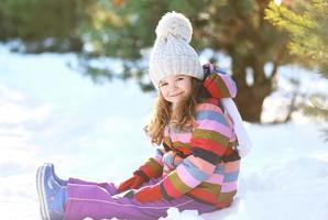 piccolo bambino seduto sulla neve divertendosi in inverno