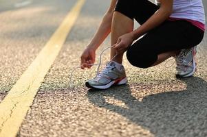 giovane donna fitness legare i lacci delle scarpe sulla strada