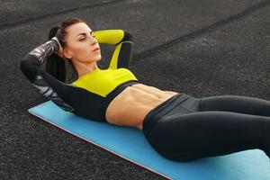 donna fitness facendo sit up lavorando. ragazza che esercita gli addominali