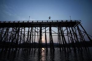 il giovane ragazzo sagoma che salta del vecchio ponte di legno