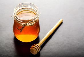 barattolo di miele e mestolo contro foto