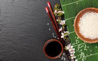 bacchette sushi giapponesi, ciotola di salsa di soia, riso e fiori di sakura foto