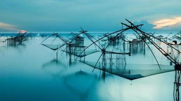 silhouette del metodo di pesca tradizionale utilizzando un quadrato di bambù d foto