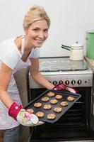 donna sorridente mettendo un vassoio di biscotti in forno foto