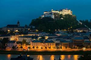 Salisburgo con la fortezza di Hohensalzburg di notte, Austria foto