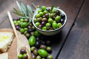 olio d'oliva e pane sul tavolo in legno rustico foto