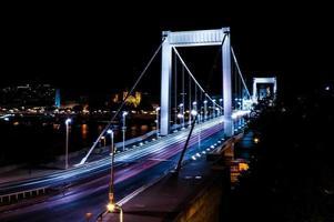 sentieri di semaforo in un ponte bianco di notte
