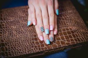 manicure femminile su uno sfondo di pelli di coccodrillo