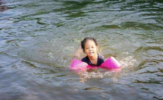 piccola ragazza asiatica che nuota nel fiume