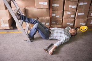 lavoratore sdraiato sul pavimento in magazzino