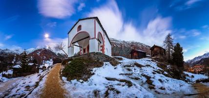 chiesa bianca sulla collina e picco del cervino prima dell'alba