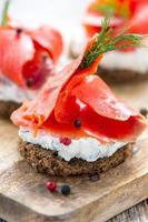 panino di pane nero, formaggio alle erbe e salmone rosso. foto