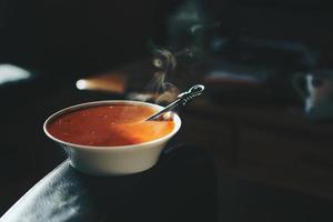 ciotola di zuppa di pomodoro su un bracciolo di un divano in pelle foto