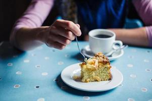 donna che mangia caffè e torta nella sala da tè foto