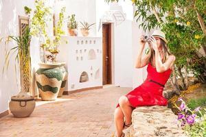 donna felice è seduta per strada e scattare foto.