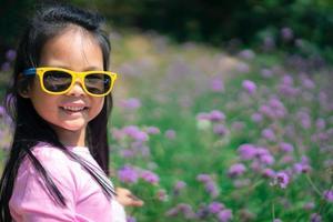 bambina asiatica in abito rosa che indossa occhiali da sole